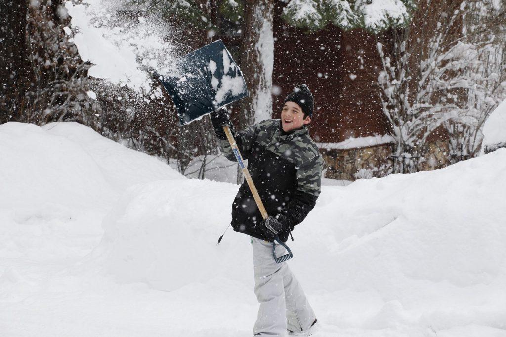 young boy lifting snow shovel over head